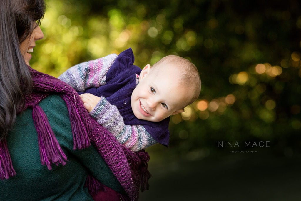 baby peeping over shoulder being photographed in Surrey