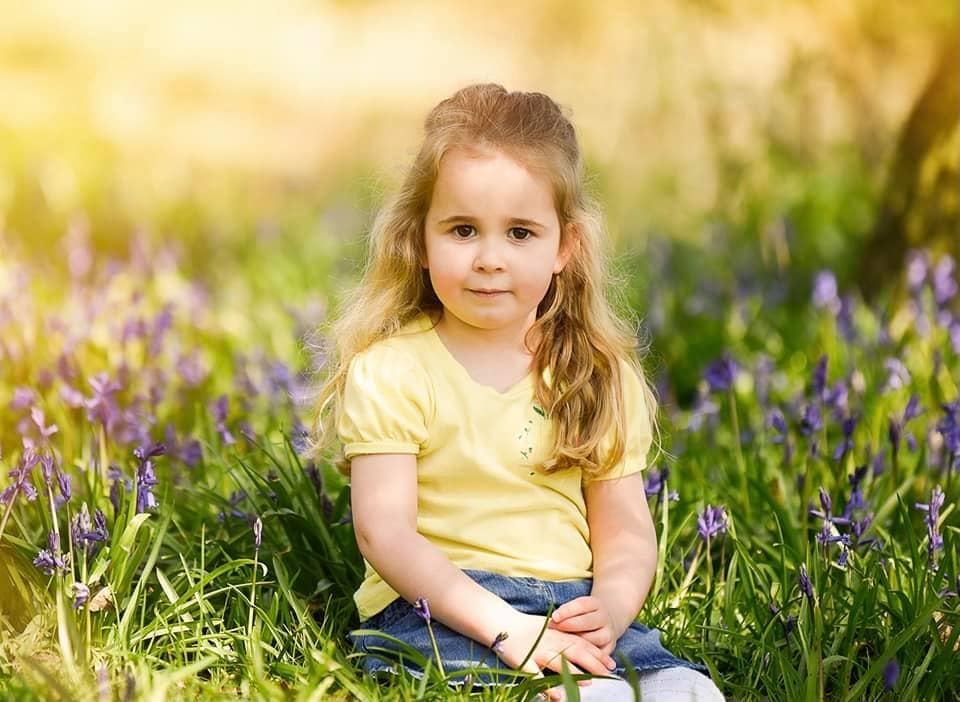 Little girl in yellow top sitting in the bluebells