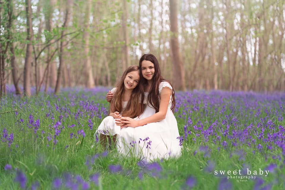 sisters being photographed in the bluebells